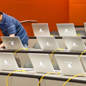 Image of man setting up a bunch of laptops