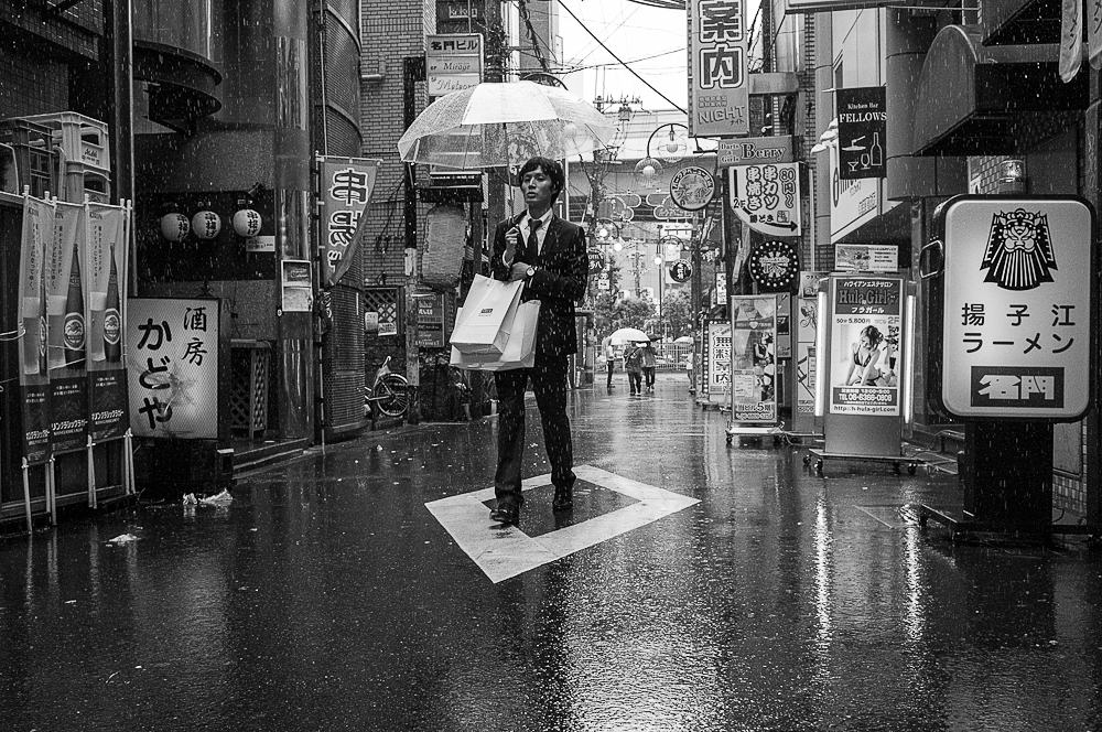 Man walking under the rain in a Japanese city