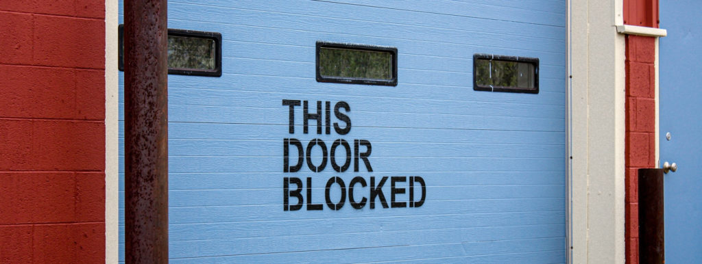 Photo of a garage door with the inscription 'this door blocked'