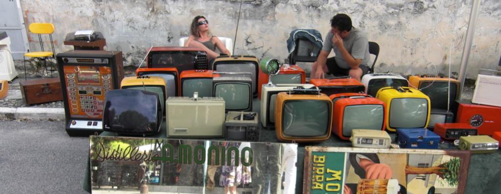 Fotografía de dos personas ante muchos televisores antiguos